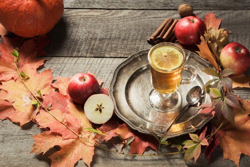 Taza que se calienta de té con la decoración de las hojas y de las calabazas de otoño en el tablero de madera Todavía de la caída foto de archivo