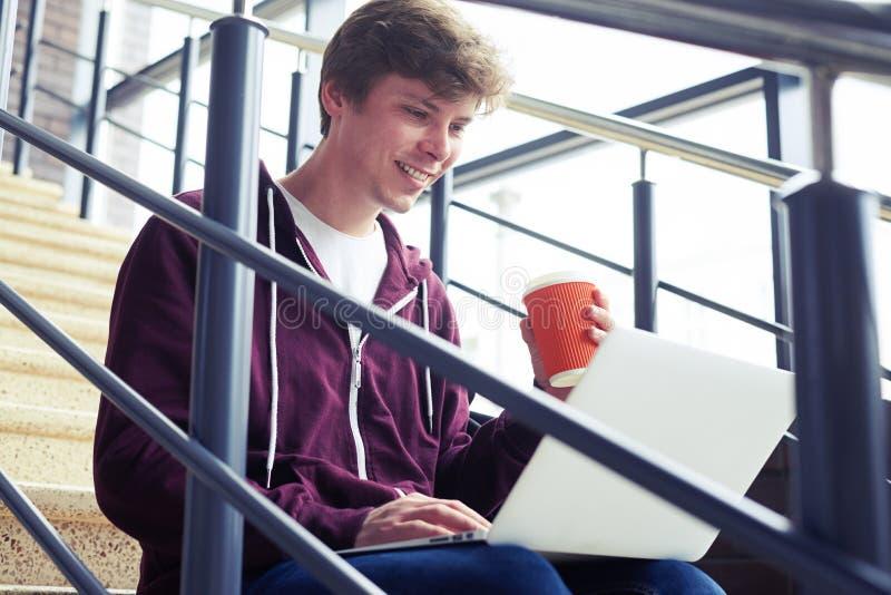 Taza que se sostiene masculina contenta de café y de charla en ordenador portátil imágenes de archivo libres de regalías