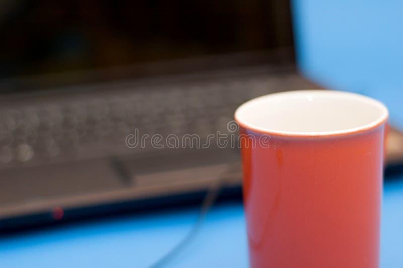 Taza roja con el cuaderno fotografía de archivo