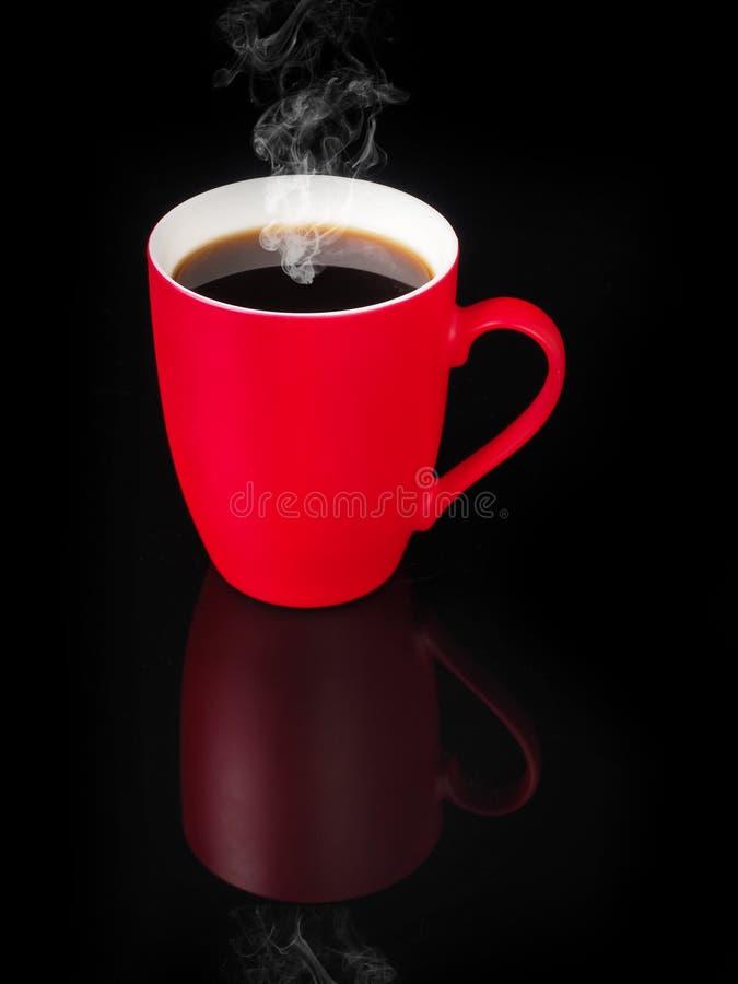 Taza roja con la reflexión en fondo negro foto de archivo