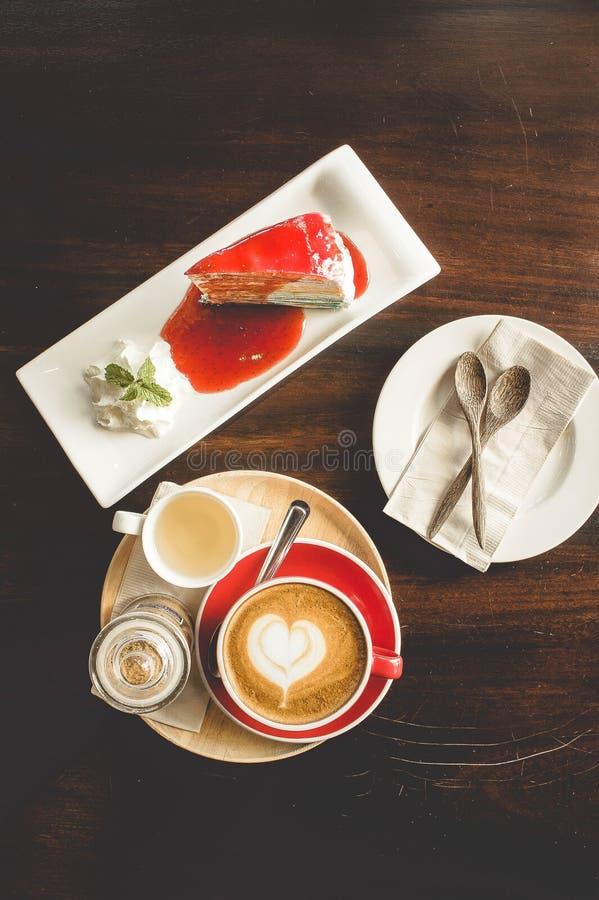 Taza roja del café y torta sabrosa en el tiempo del café del vintage del café foto de archivo libre de regalías