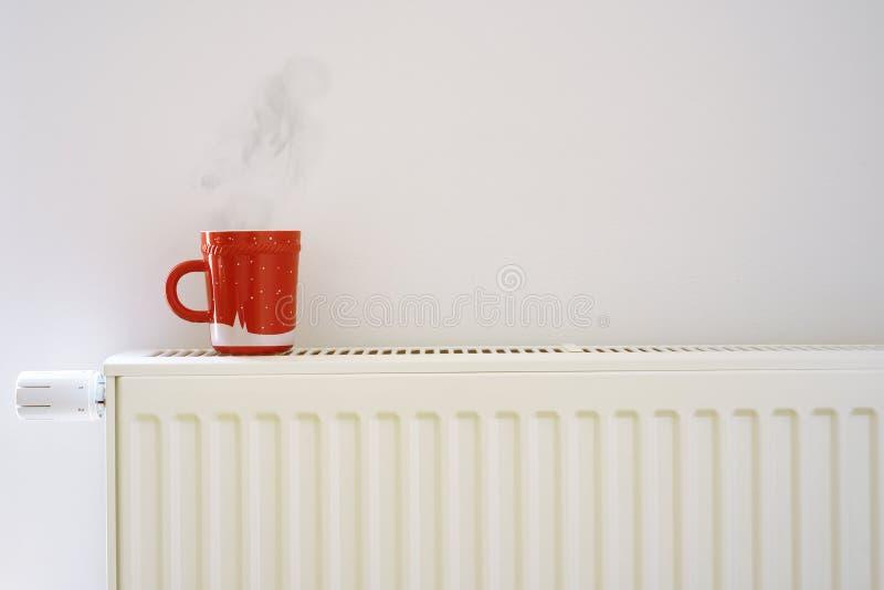 Taza roja en el radiador de la calefacción fotos de archivo