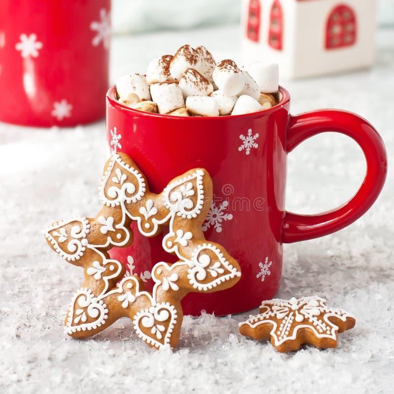 Taza roja llenada del chocolate caliente, de las melcochas y de las galletas del pan de jengibre en fondo ligero imagen de archivo