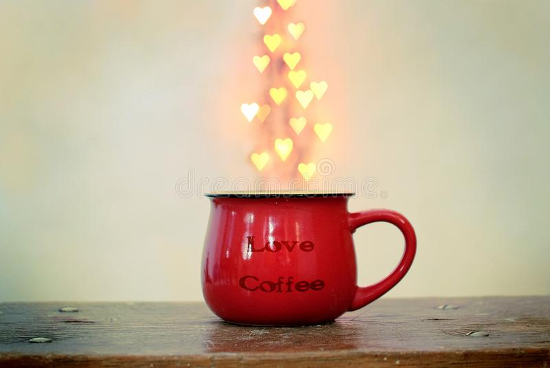 Taza roja y bokeh en forma de corazón sobre él en el fondo blanco Concepto del café del amor fotografía de archivo libre de regalías