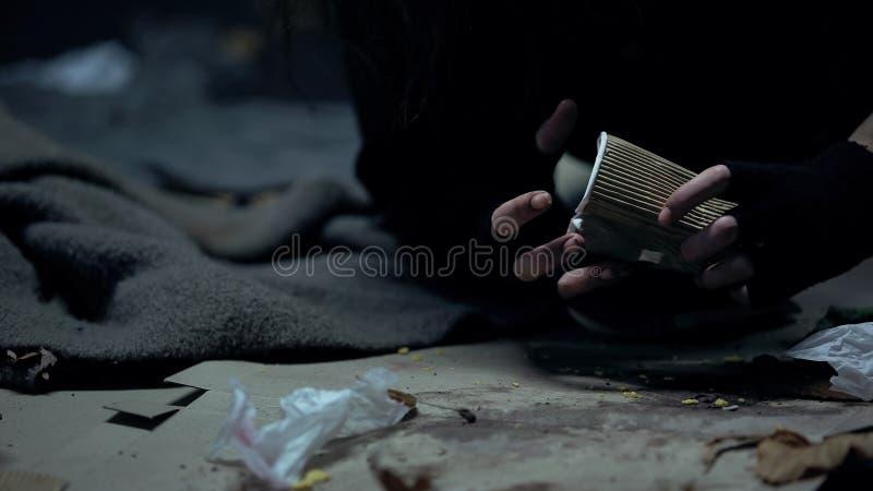 Taza sucia sin hogar del mendigo de la tenencia de la mujer en el lugar oscuro, problemas sociales, caridad fotos de archivo libres de regalías