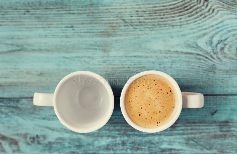 Taza vacía y llena de café fresco en la tabla del azul del vintage imagen de archivo libre de regalías