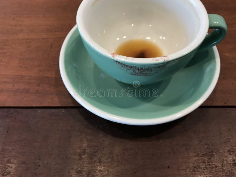 Taza verde acabada de café caliente con la marca roja del lápiz labial en café imágenes de archivo libres de regalías