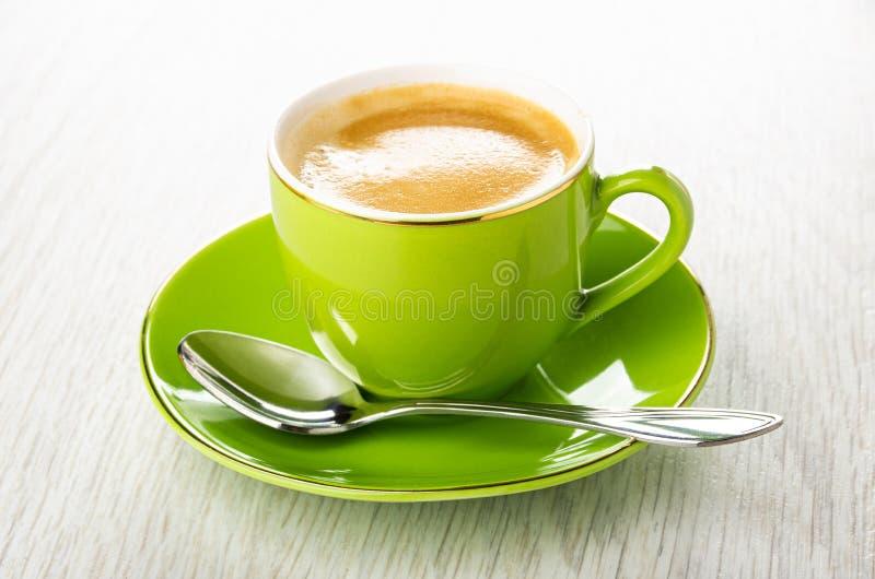 Taza verde con el café, cuchara en el platillo en la tabla de madera fotos de archivo