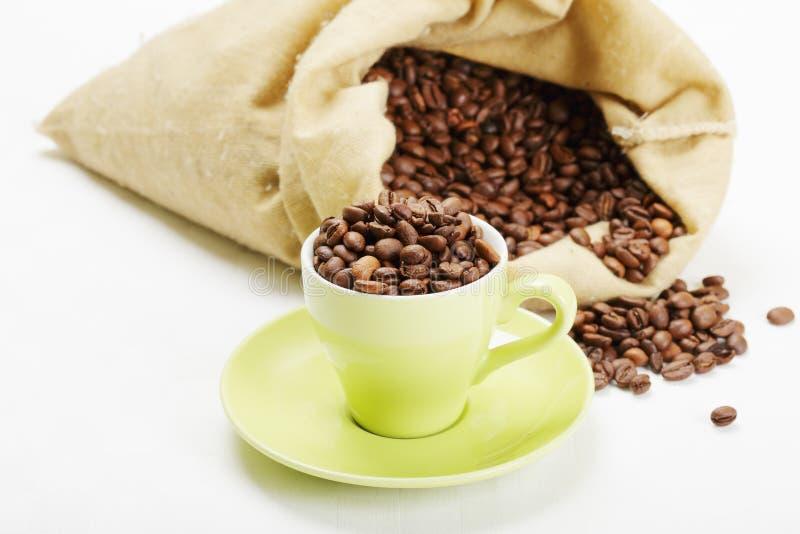 Taza verde con los granos de café fotos de archivo
