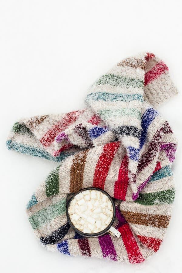 Taza vieja de cacao caliente con melcochas y un knitt colorido suave imagenes de archivo