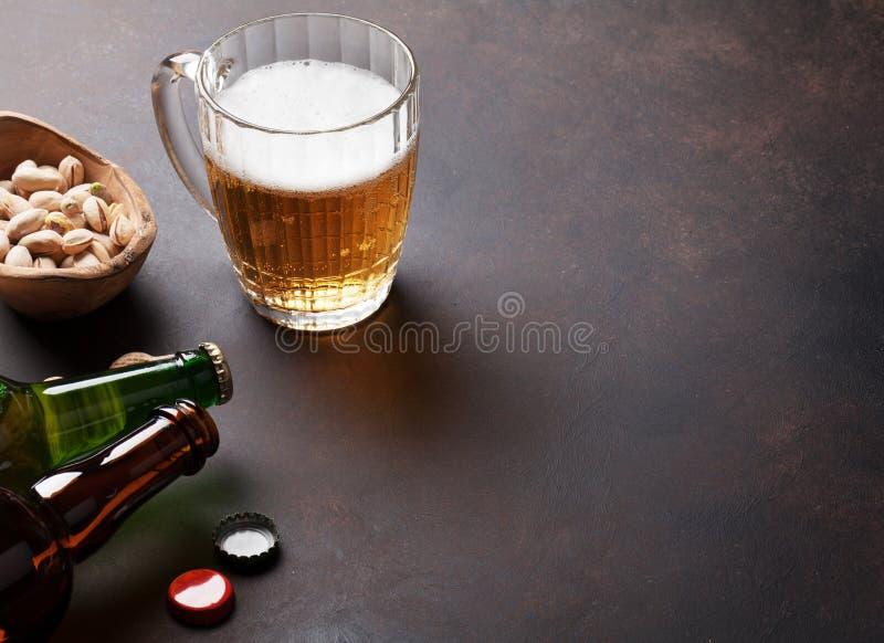 Taza y bocados de cerveza de cerveza dorada fotografía de archivo libre de regalías