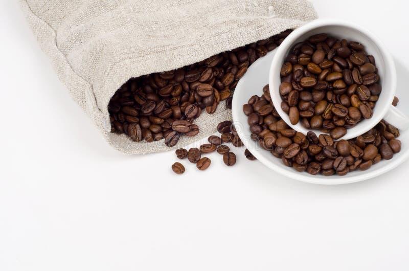 Taza y bolso con los granos de café en fondo gris fotografía de archivo