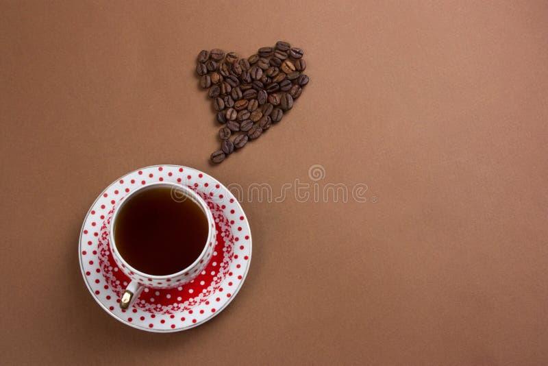 Taza y corazón del café sólo con los granos de café en el fondo marrón, espacio de la copia fotos de archivo libres de regalías