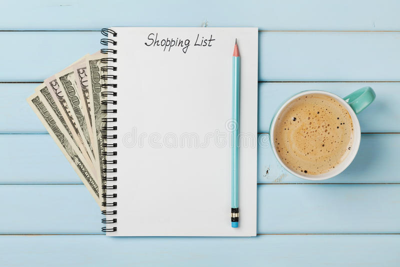 Taza y cuaderno de café con la lista de compras y el dólar del dinero del efectivo en la tabla rústica azul fotografía de archivo