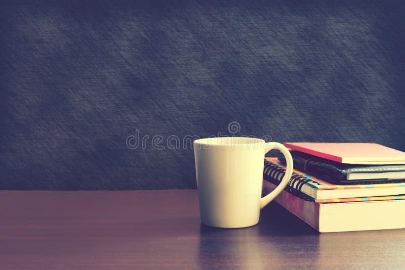 Taza y cuaderno de café en la tabla de madera con el fondo del tablero trasero foto de archivo