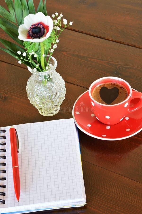 Taza y cuaderno de notas manchados rojos imagen de archivo libre de regalías
