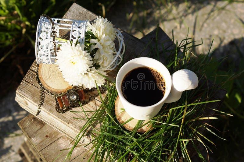 Taza y flores de café imagenes de archivo