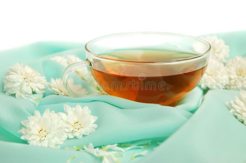 Taza y flores de cristal de té fotos de archivo libres de regalías