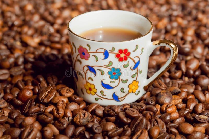 Taza y fondo de café con los granos de café fotos de archivo libres de regalías
