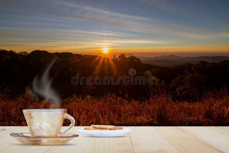 Taza y galleta calientes de café en la sobremesa de madera en prado borroso y la montaña con salida del sol y fondo de la llamara foto de archivo libre de regalías