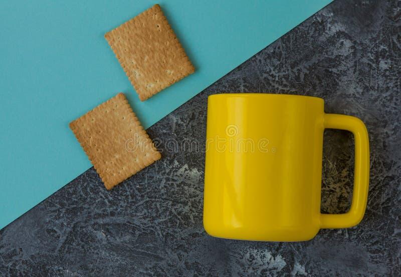 Taza y galletas amarillas en la tabla de piedra oscura y el papel azul con el espacio de la copia imagen de archivo
