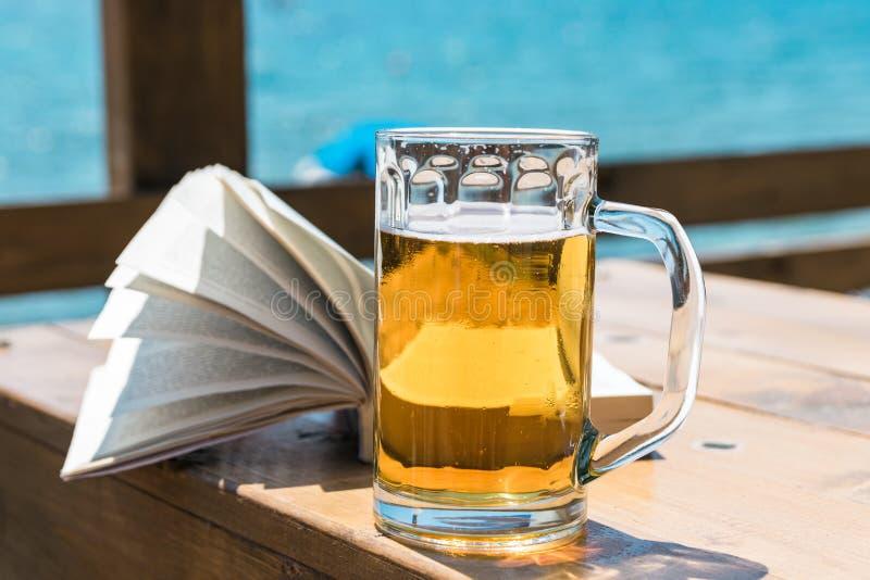 Taza y libro de cerveza en la tabla, con el mar/el océano en el fondo fotografía de archivo libre de regalías