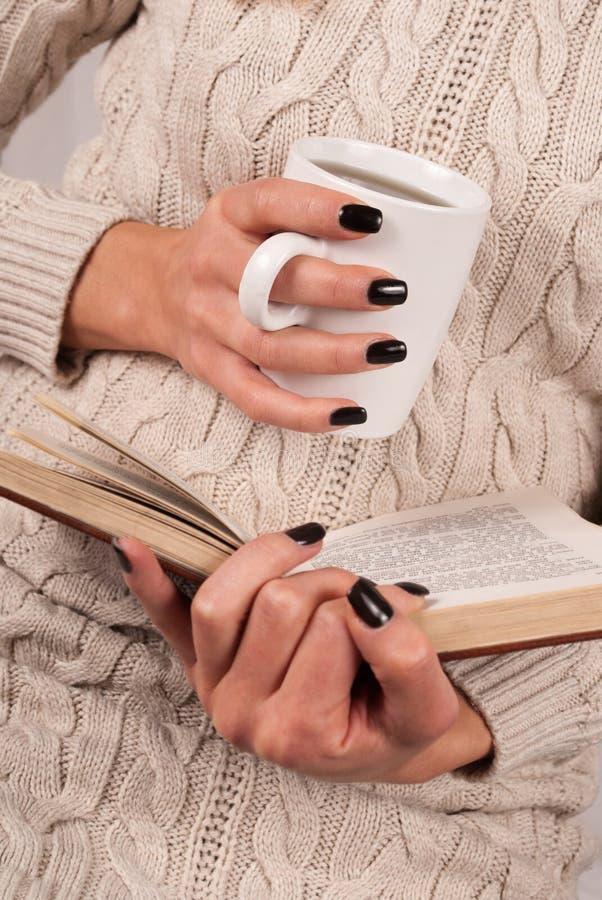 Taza y libro de té en manos de la muchacha con los clavos negros foto de archivo libre de regalías