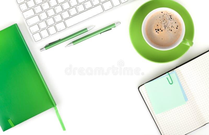 Taza y materiales de oficina verdes de café fotografía de archivo