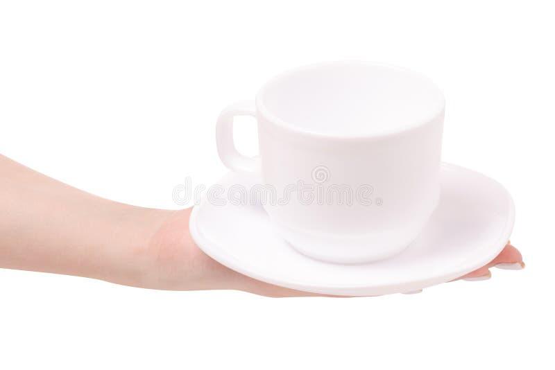 Taza y platillo blancos en una mano femenina fotografía de archivo libre de regalías