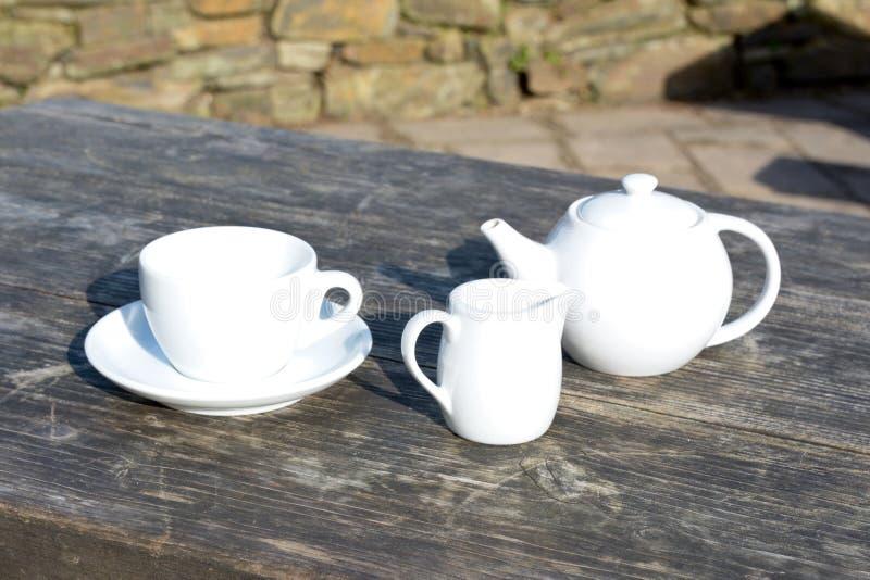 Taza y platillo de té del pote del té más un jarro de leche en la tabla de madera del café imagenes de archivo
