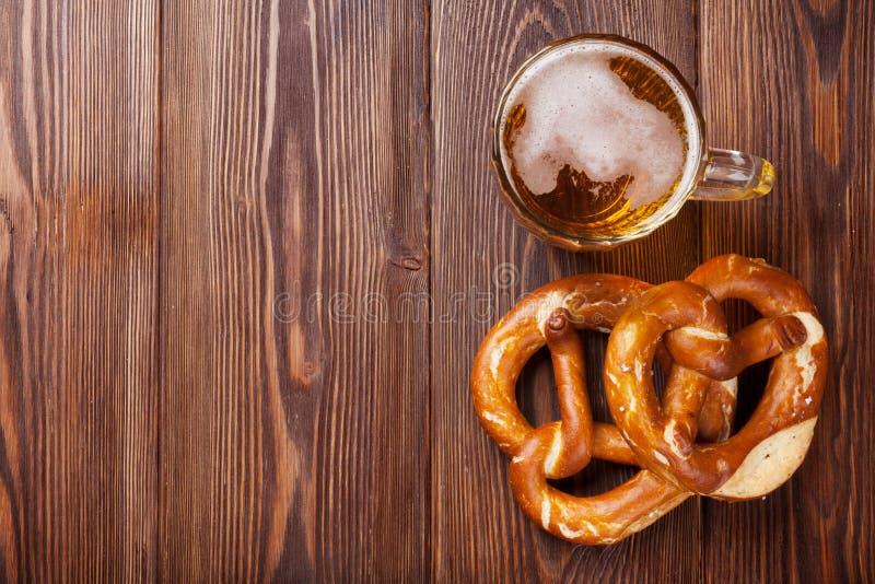 Taza y pretzel de cerveza en la tabla de madera imágenes de archivo libres de regalías