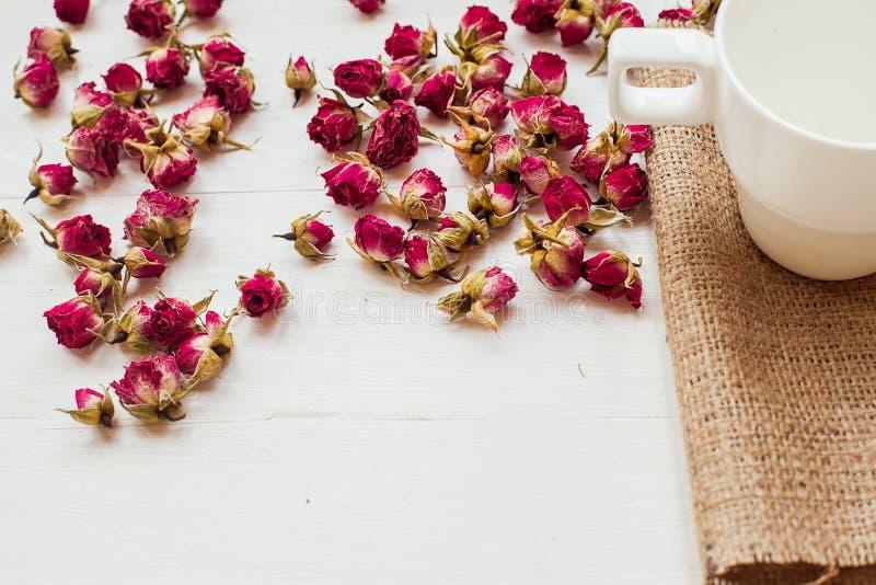 Taza y rosas secas imagen de archivo