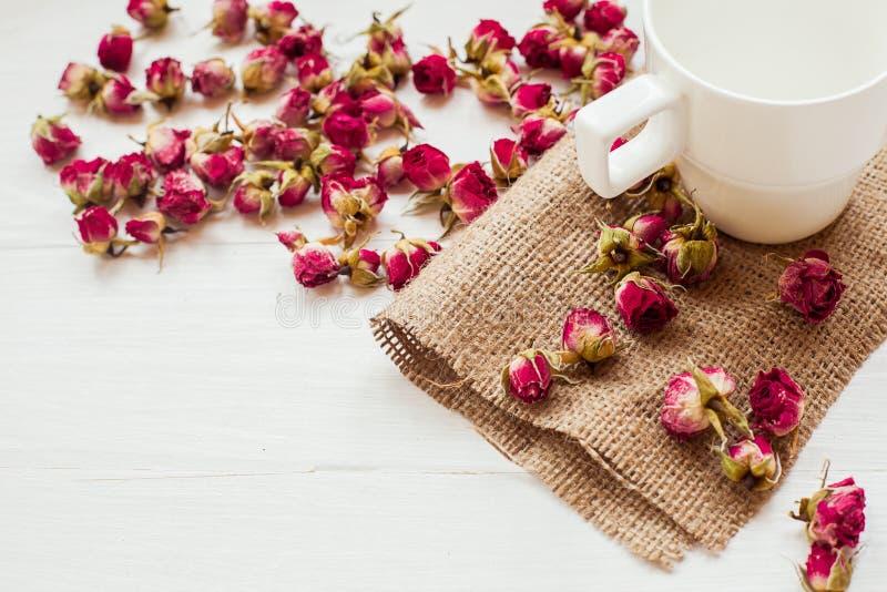 Taza y rosas secas en la tabla foto de archivo
