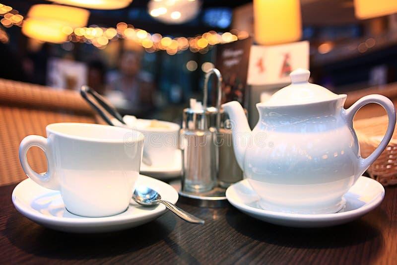 Taza y tetera en café imagen de archivo libre de regalías