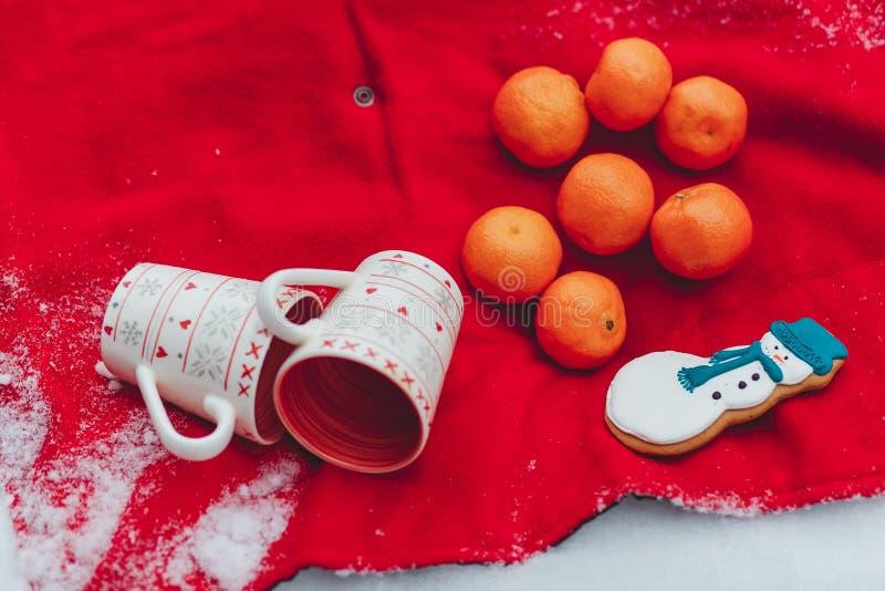 Tazas blancas rojas del ornaiment de la Navidad - todavía de la Navidad vida Naranjas y pan de jengibre del muñeco de nieve en la imagen de archivo libre de regalías