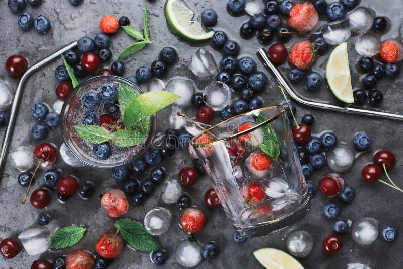 Tazas con agua de soda helada en fondo oscuro con la paja, la menta, las hierbas, las bayas, el hielo y el humo del metal del eco fotos de archivo