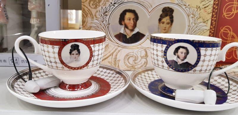 Tazas con la imagen de Pushkin en el contador de la tienda - un recuerdo para las fans del poeta imagenes de archivo