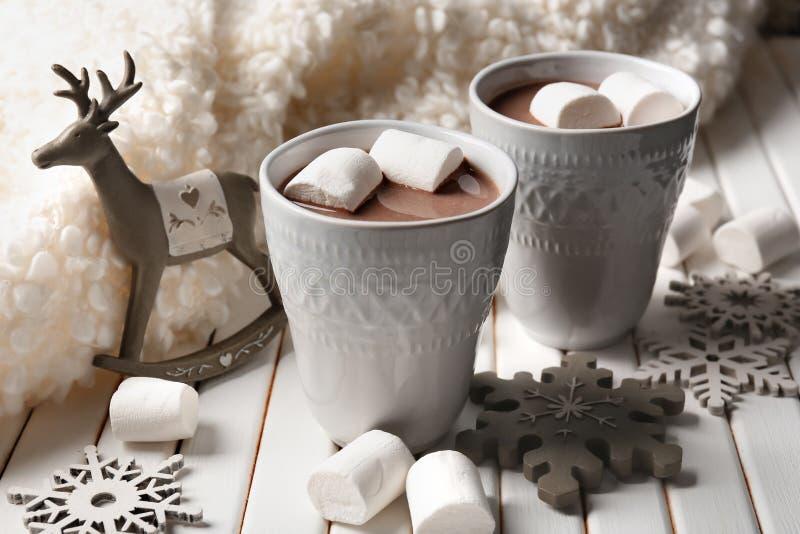Tazas de cacao caliente con las melcochas y las decoraciones de la Navidad en la tabla de madera imagen de archivo libre de regalías