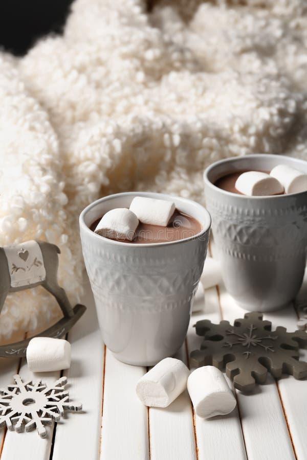 Tazas de cacao caliente con las melcochas y las decoraciones de la Navidad en la tabla de madera foto de archivo libre de regalías