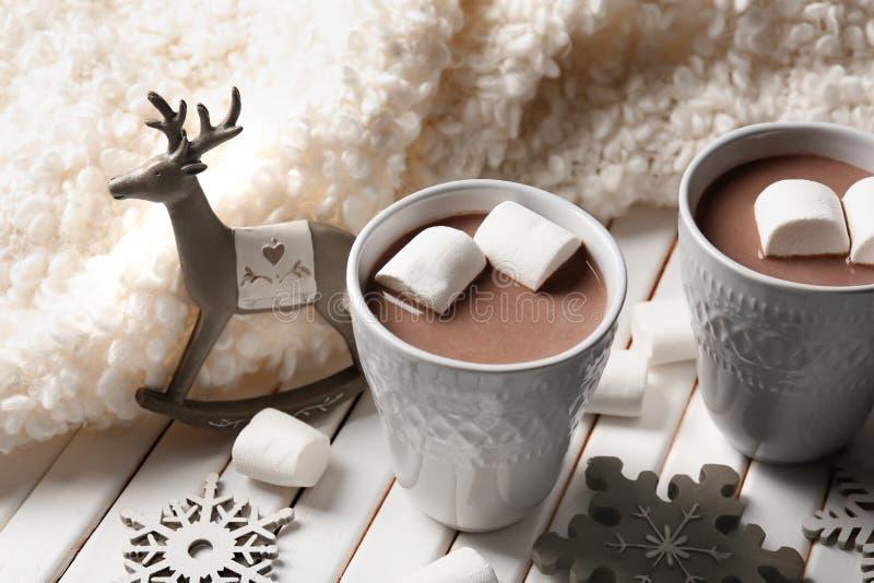 Tazas de cacao caliente con las melcochas y las decoraciones de la Navidad en la tabla de madera fotografía de archivo