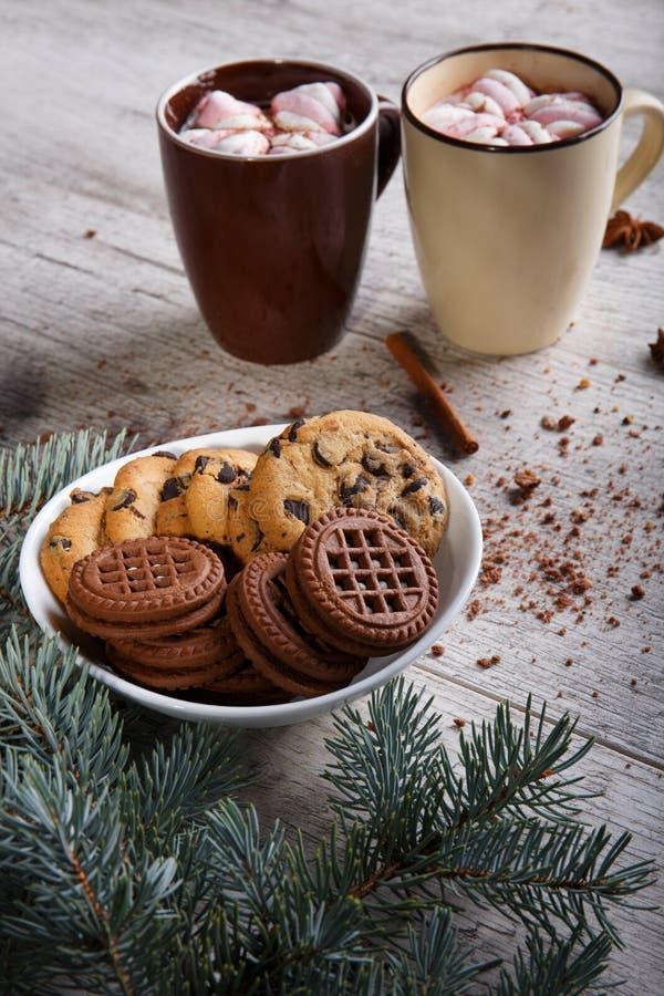 Tazas de cacao con las melcochas y las galletas del chocolate en un fondo de la tabla Dulces de la Navidad Desayuno del café fotografía de archivo libre de regalías