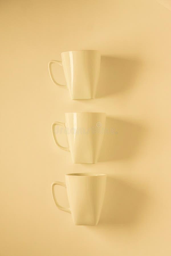 3 tazas de café amarillas en el fondo amarillento en una fila vertical, espacio vacío de la copia imagen de archivo libre de regalías