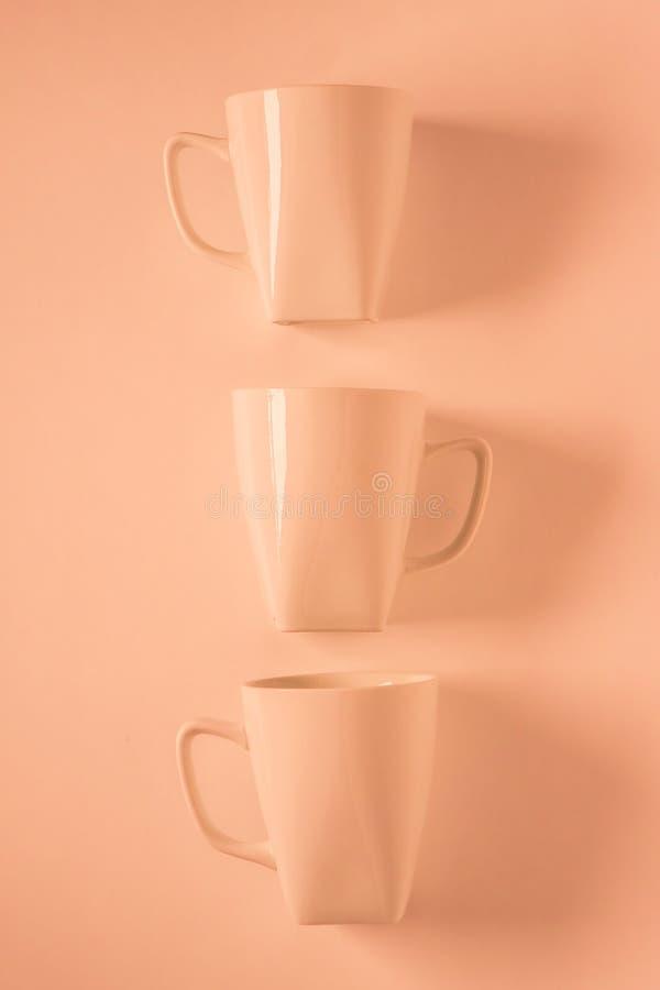 3 tazas de café anaranjadas en fondo anaranjado en una fila vertical con el copyspace vacío imagen de archivo libre de regalías
