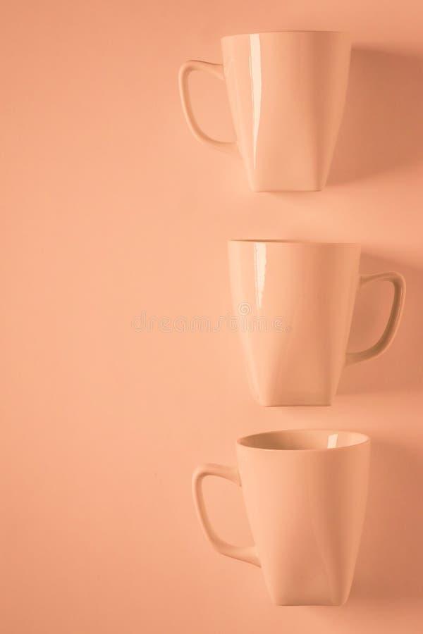 3 tazas de café anaranjadas en fondo anaranjado en una fila vertical con el copyspace vacío imagen de archivo