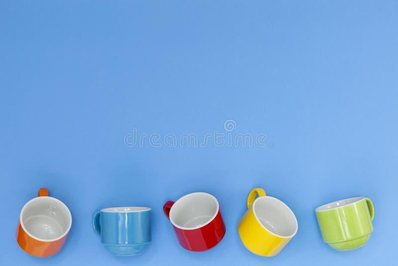 tazas de café coloridas en fondo azul imagenes de archivo