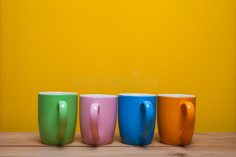 Tazas de café coloridas en la tabla de madera sobre fondo amarillo fotos de archivo libres de regalías