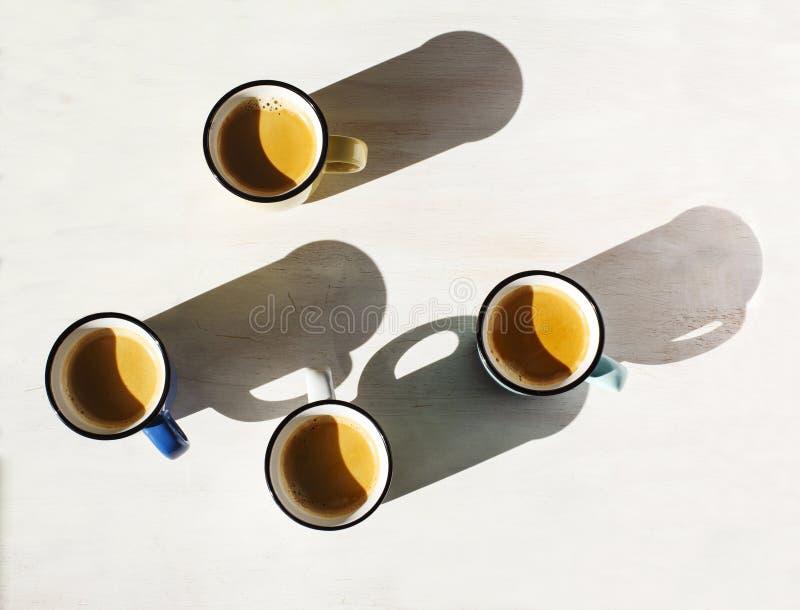 Tazas de café Cuatro tazas de café express en una tabla detrás encendido por el lanzamiento del sol sombras largas imágenes de archivo libres de regalías