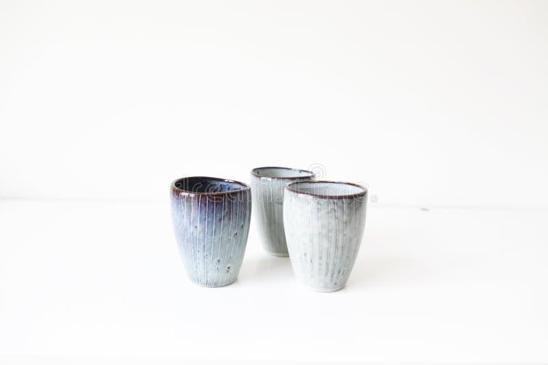 Tazas de café de la cerámica de la naturaleza en la tabla blanca imagen de archivo
