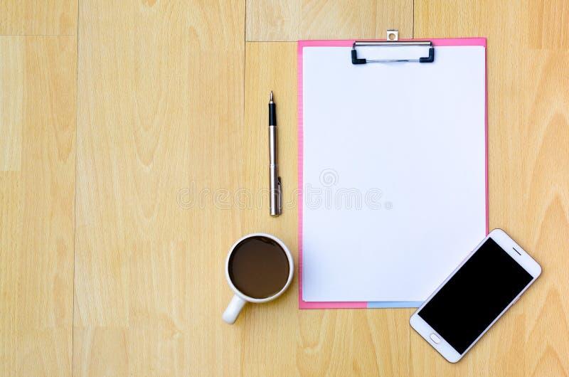 Tazas de café del teléfono de la maqueta, papel de nota de los auriculares colocado en un woode imagen de archivo libre de regalías