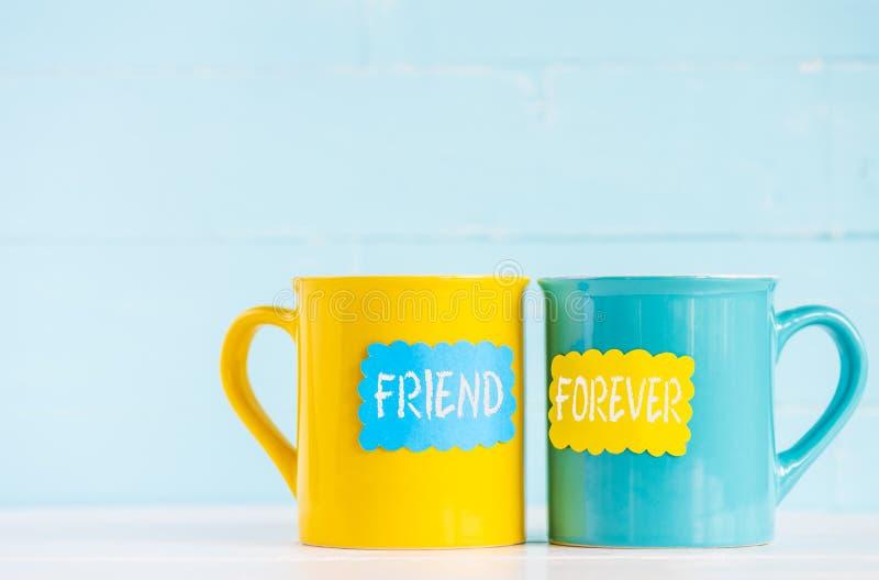 Tazas de café en la tabla de madera con la etiqueta y los amigos de papel para siempre imagen de archivo